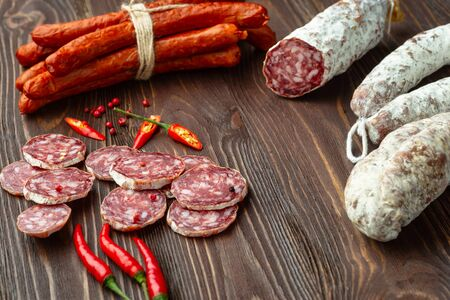 Sliced smoked sausage with hot spices and chilly pepper on dark rustic background. Meat food concept.