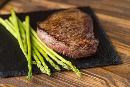 Hot delicious barbecued beef steaks with stripes served with grilled asparagus on black slate plate, horizontal view from above, close-up