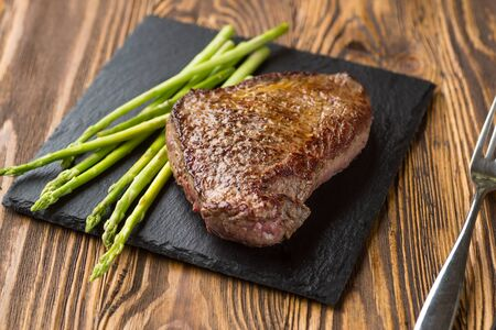 Heiße köstliche gegrillte Rindersteaks mit Streifen serviert mit gegrilltem Spargel auf schwarzer Schieferplatte, horizontale Ansicht von oben, Nahaufnahme