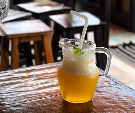 A glass of fresh ice cold lemonade on wooden table of coffee shop patio Close up of refreshing orange juice cold beverage on the cafe terrace, outside. Text copy space 写真素材