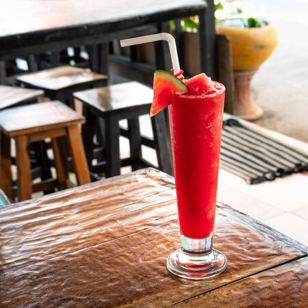 Fresh organic watermelon smoothie in glass on table in cafe, close up. Refreshing tropical fruit drink. The concept of healthy eating.