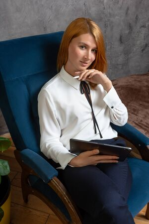 Business woman at home after work using tablet, sitting on the chair. Looking at camera,