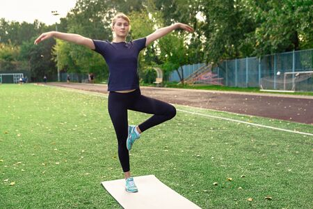 Young woman practicing yoga outdoors at park standing in one legged prayer pose meditating.
