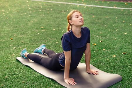 Yoga outdoor. Young woman doing yoga exercises,  practicing yoga on the grass. Concept of healthy lifestyle and relaxation.