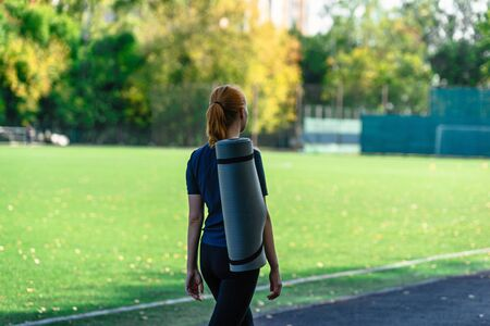 Young  woman with yoga mat walking to training in park. Beautiful sporty fitness model during outdoor workout.