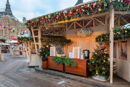 New Year lights of illuminated fair pavilions offering handmade souvenirs, sweets and Russian hot drinks at the entrance to the Christmas market