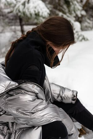 Outdoors lifestyle portrait of sitting stunning young woman. Wearing silver down jacket and black pullover. Snowy cold winter.