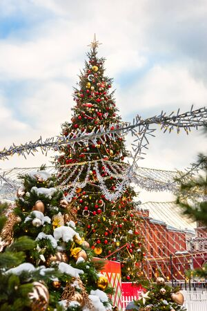 Christmas tree. Decorated festive Christmas tree in snow, balls and toys. Ornamental, exterior cozy atmosphere of holidays, sky background. 写真素材