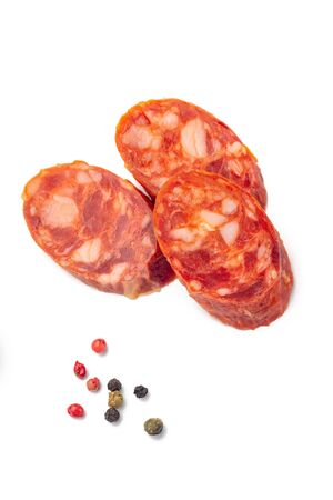 Traditional Catalan thin dry cured pork sausage Fuet with sliced pieces with pepper. Isolated over white background