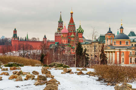Beautiful winter cityscape with the view from Zaryadye park on the covered snow Spasskaya Tower (Savior's Tower) of Moscow Kremlin and St. Basil's Cathedral framed by white trees.