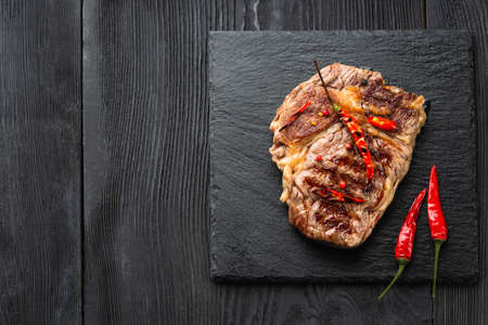 Sliced medium rare grilled steak on rustic stone board with chili and spices , dark rustic wooden background, top view, place for text