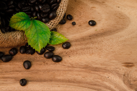 coffee beans in sack on wooden background photo