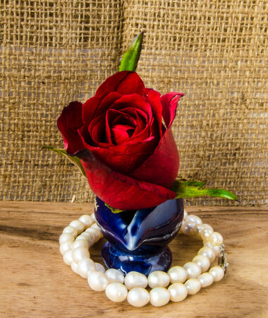 element design of red rose and pearl on wooden floor and sack texture background photo