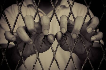 locked up in a cage: closeup on hands of man in cage , color filter process