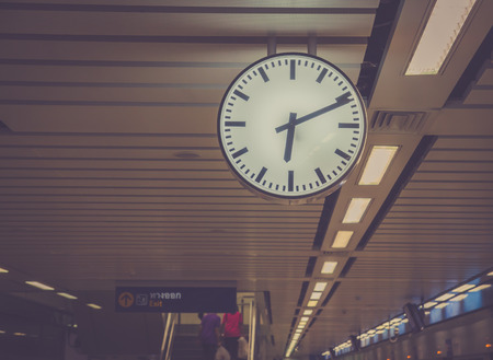 under ground: modern clock in under ground train with color filter on vintage styled Stock Photo