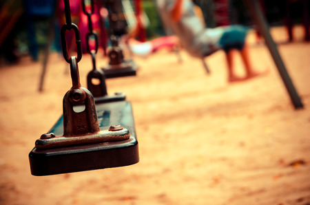 jungle gyms: chain swings on playground with blur kid on park, vintage tone color