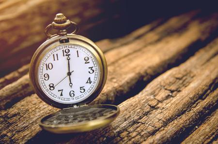 12 o clock: vintage pocket watch on grunge wooden board