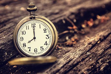 12 o clock: vintage pocket watch on grunge wood log