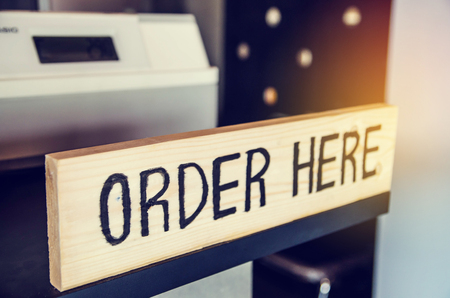 order here: order here sign on wood panel Stock Photo