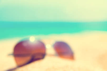 blurred abstract Fashion sunglass on the summer beach at ocean background , vintage filter , Summer vacation actually relaxing, summer concept , vocation time , summer background Stock Photo