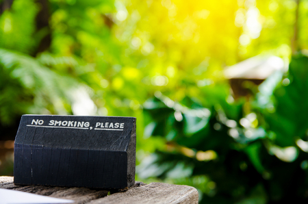 a public notice: no smoking sign on wood board in coffee shop Stock Photo