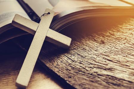 Primo piano della collana semplice croce di legno sulla bibbia cristiana, il tono vintage, dio