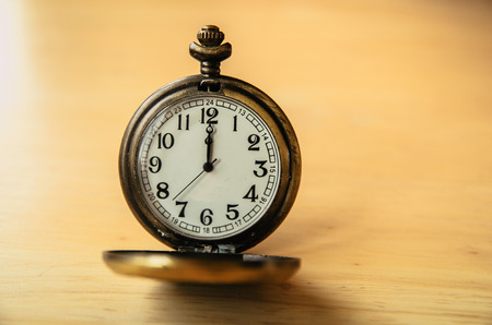 hands in pocket: Old pocket watch on wooden table