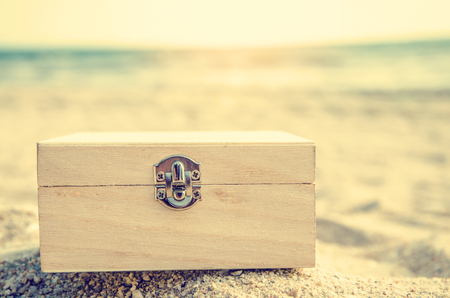 treasure chest on sand beach with blurred sea background