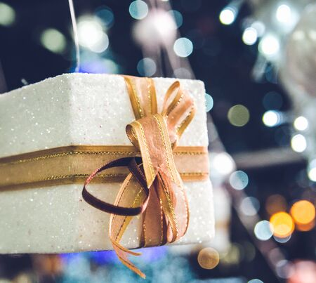 christamas: white Christmas gift box  with gold ribbon  and copyspace for your greeting or wishes