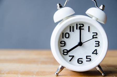Retro alarm clock on a table. Photo in retro color image style Stock Photo