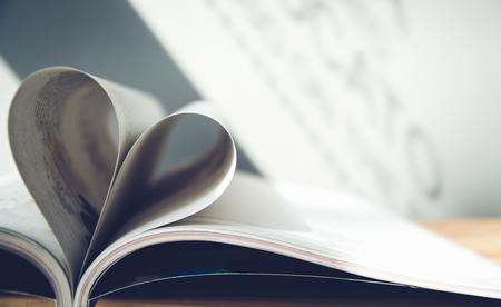 心臓の形を形成する本のページ。velantine (愛)