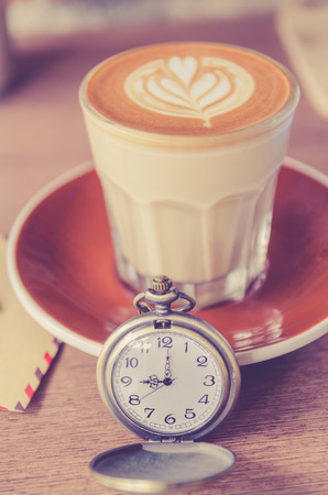vintage pocket watch with coffee latte art on wood teble in cafe