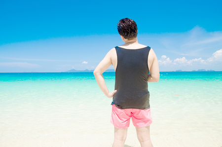 sexy gay: backside of man with black vest and pink shorts on blue sea background