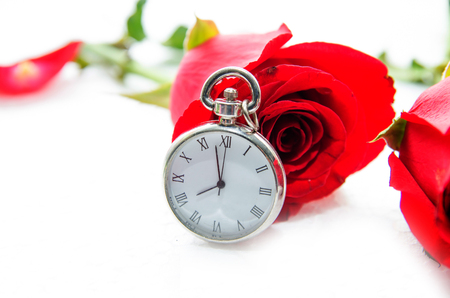 white fabric texture: Red Rose and a pocket watch on a napkin embroidered with a cross Stock Photo