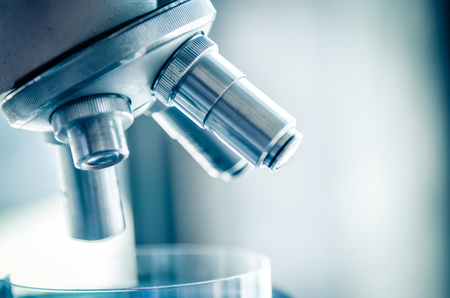 Close-up shot of microscope with metal lens at laboratory. Scientific and healthcare research background.