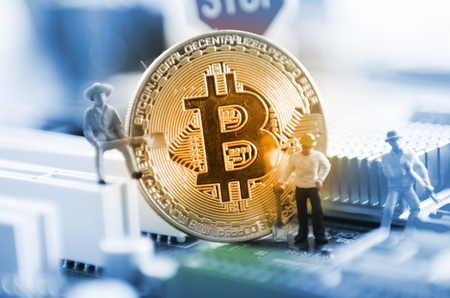 Marco shot of bitcoin and minner worker man , figures working on group of bitcoins. virtual cryptocurrency mining concept Archivio Fotografico