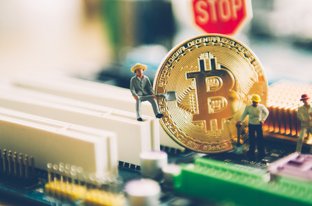 Marco shot of bitcoin and minner worker man , figures working on group of bitcoins. virtual cryptocurrency mining concept Standard-Bild