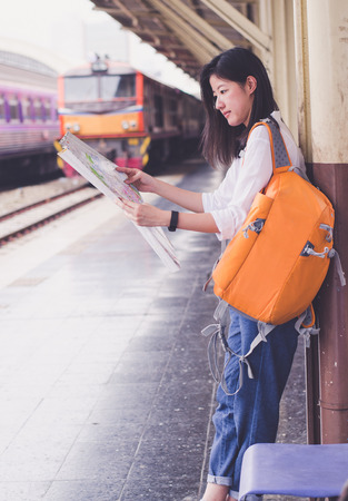 young women hold map on hand in train station