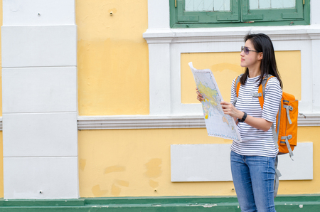 Young traveler with map on street building background