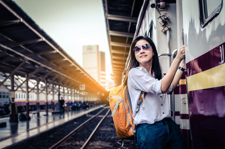 Girl wearing backpack holding map, waiting for a train. Traveling in Bangkok Thailand. Travel concept