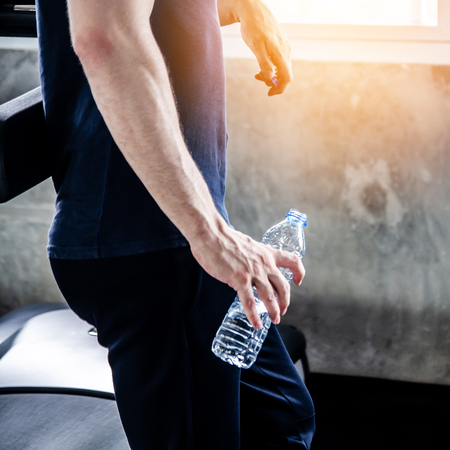Unrecognizable young man in sportswear running on treadmill at gym and holding bottle of water Stock Photo