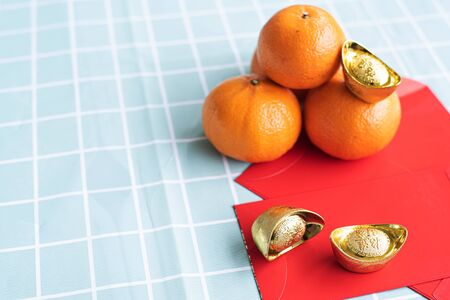 Accessories on Lunar New Year & Chinese New Year vacation concept background.Orange in white plate with red pocket money