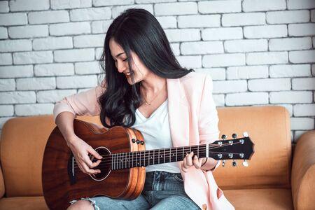 woman playing guitar on sofa .