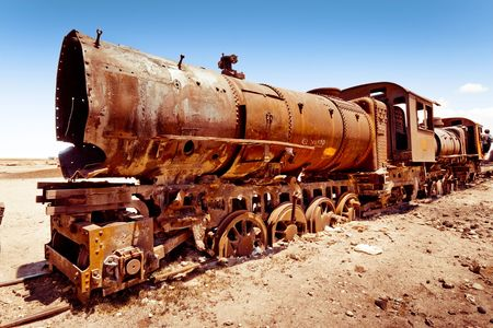 Graveyard of rusty old steam trains in middle of Bolivian desert near Uyuni photo