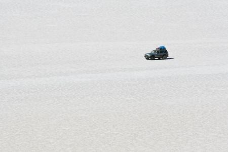 vastness: car crossing the high altitude salt flats of Uyuni in Bolivian Andes