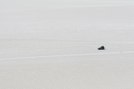 car crossing the high altitude salt flats of Uyuni in Bolivian Andes photo