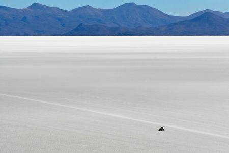 bolivian: car crossing the high altitude salt flats of Uyuni in Bolivian Andes