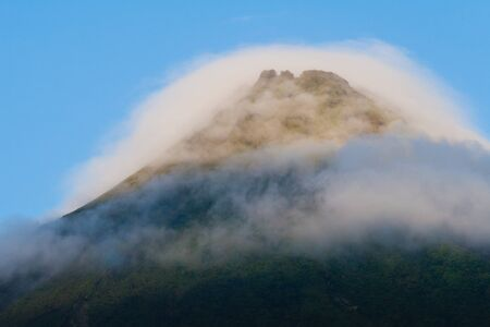 stratovolcano: Tip of Arenal Volcano in morning light, surrounded by clouds