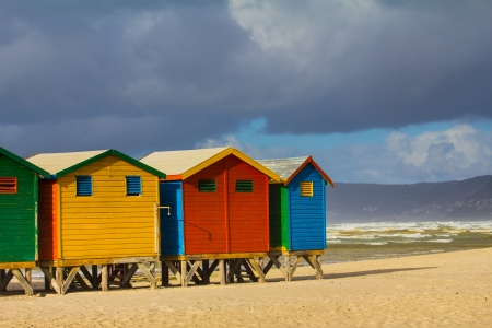 row of houses: Row of beach huts at Muizenberg beach, Cape Town, South Africa, on sunny winter day