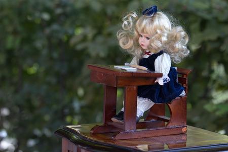 Vintage baby doll in school uniform seated at desk, sold on flea market in Slovenia